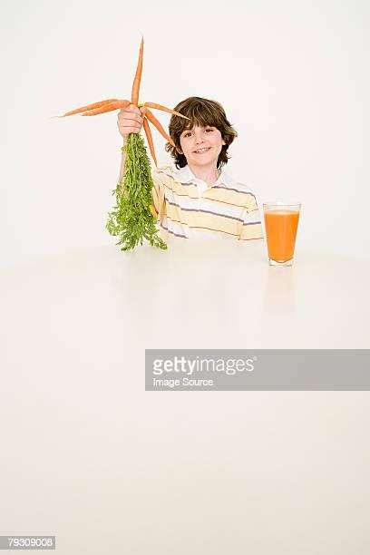 Junge hält einen Haufen Karotten