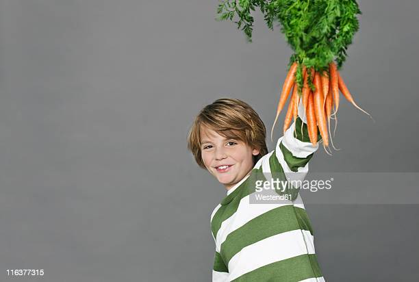 Boy holding a bunch of carrots, portrait