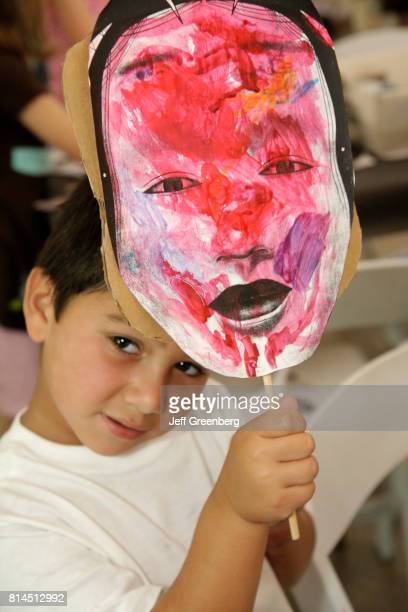 A boy holding a cardboard mask for the Asian Theme Family Day at Miami Beach Botanical Garden