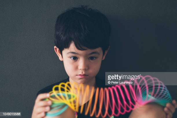 Boy holding a colourful slinky