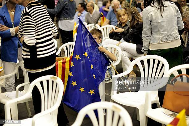 A boy holding a European flag waits for the start of the Catalan Convergence and Unity party rally marking the last day of the European Parliament...