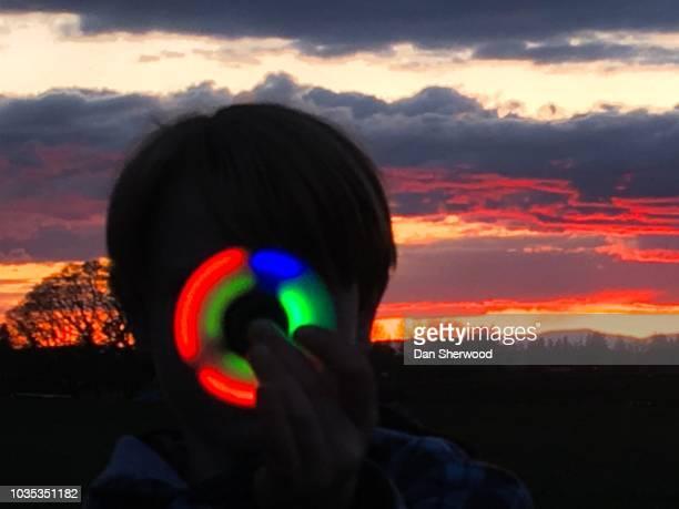 Boy Holding a Fidget Spinner at Sunset