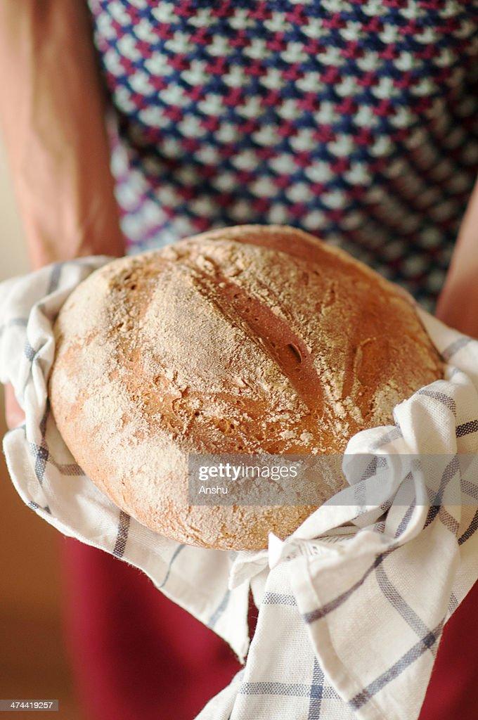 Boy holding a fresh Sourdough Bread : Stock Photo