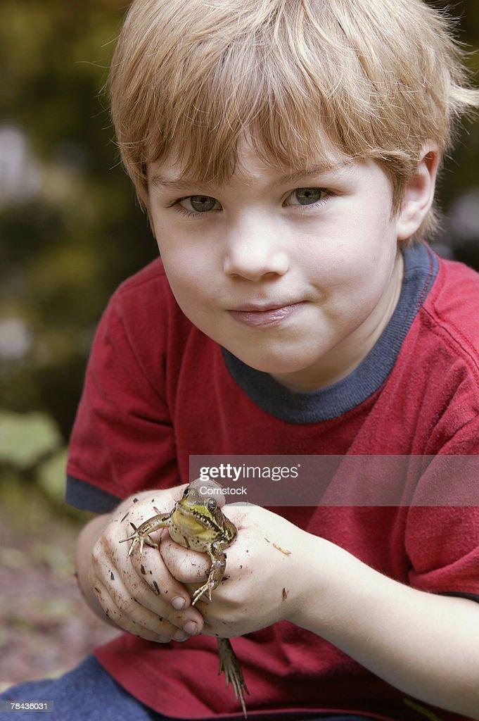 Boy holding a frog : Stockfoto