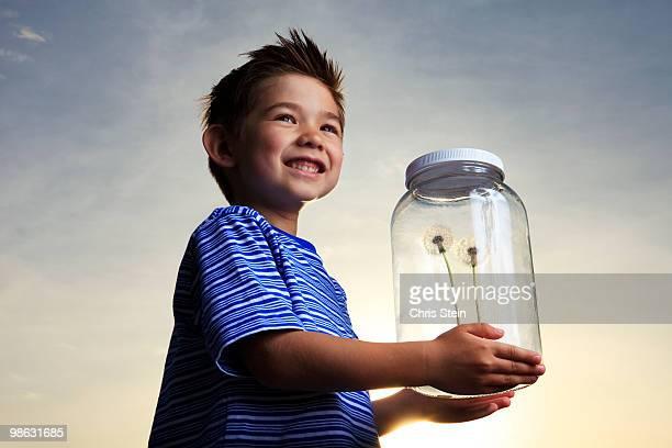Boy holding a glass jar with Dandelions