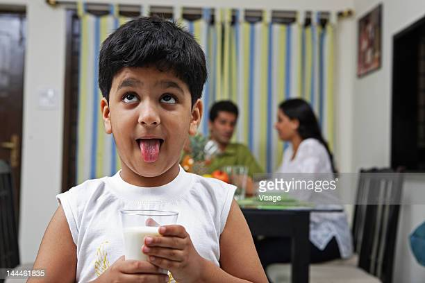 a boy holding a glass of milk and sticking his tongue out - sticking out tongue stock pictures, royalty-free photos & images