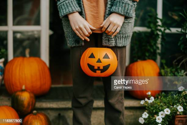 boy holding a halloween cup full of candies - trick or treat stock pictures, royalty-free photos & images