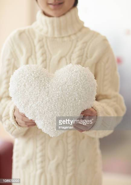 Boy holding a heart shaped cushion