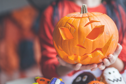 Boy holding a jack-o-lantern pumpkin decoration - gettyimageskorea