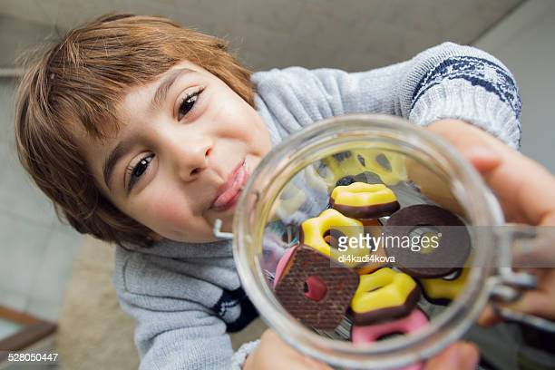 A boy holding a jar of biscuits