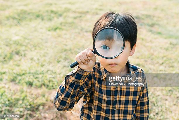 Boy holding a magnifying glass.