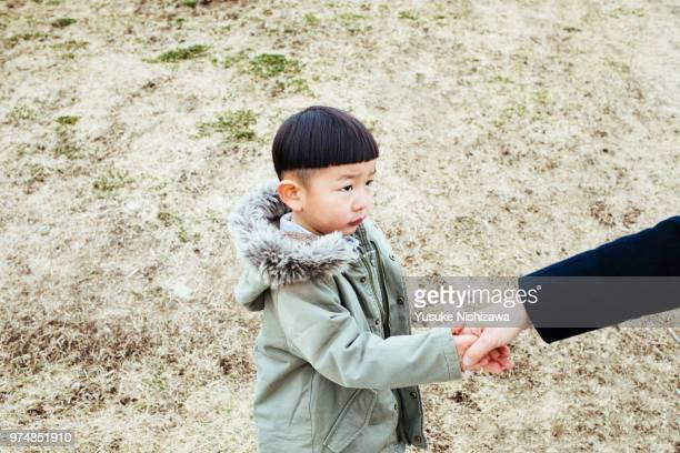 a boy holding a mother's hand - yusuke nishizawa stock pictures, royalty-free photos & images