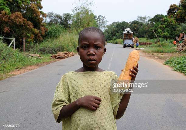 A boy holding a peace of bread stands in front of residents leaving the city of Damara 75 km north of Bangui for Bangui on December 3 2013 The...
