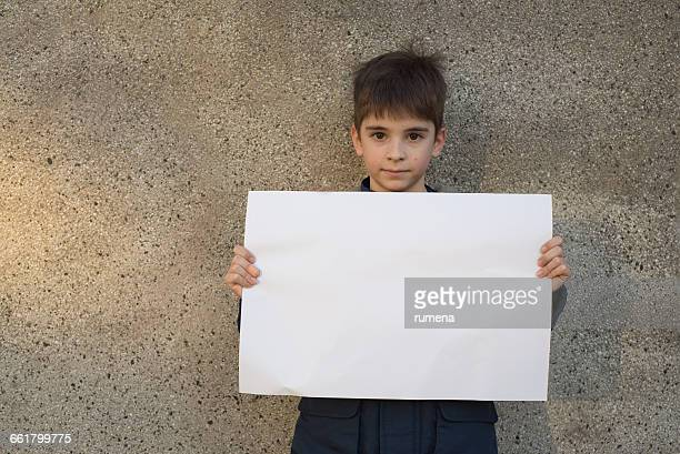 A boy holding a piece of blank paper