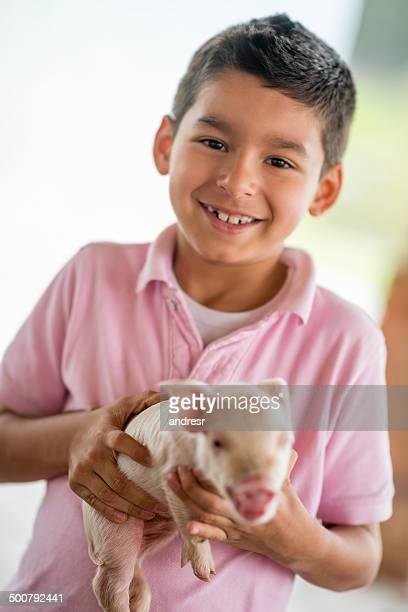 Boy holding a pig