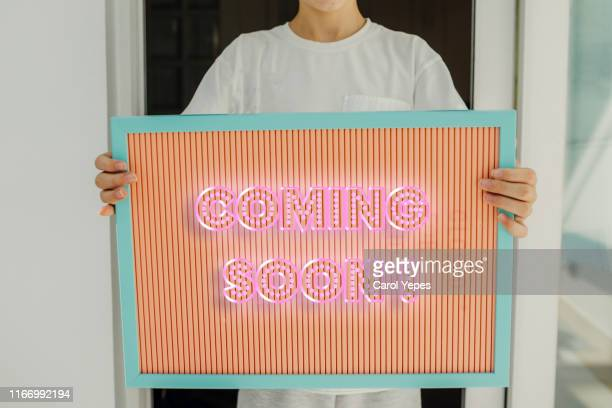 """boy holding a sign with """" coming soon"""" message - coming soon stock pictures, royalty-free photos & images"""