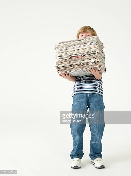 boy holding a stack of newspapers - solo un bambino maschio foto e immagini stock