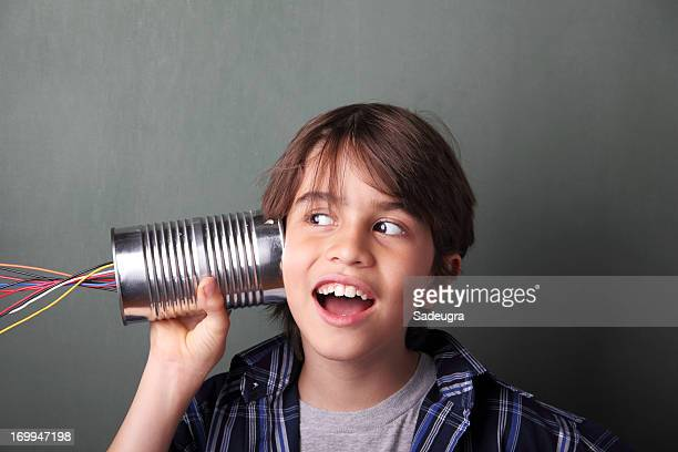 Boy holding a tin can next to eat with wires coming out