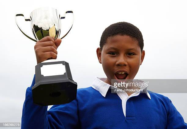 boy holding a trophy - holding trophy stock pictures, royalty-free photos & images