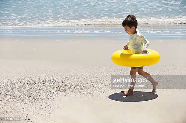 Boy holding an inflatable ring and walking on the beach