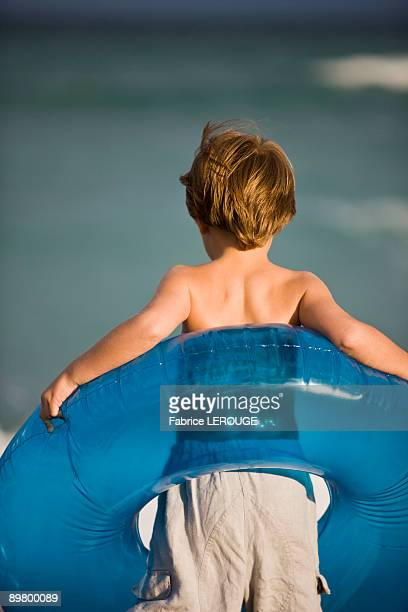 Boy holding an inflatable ring on the beach