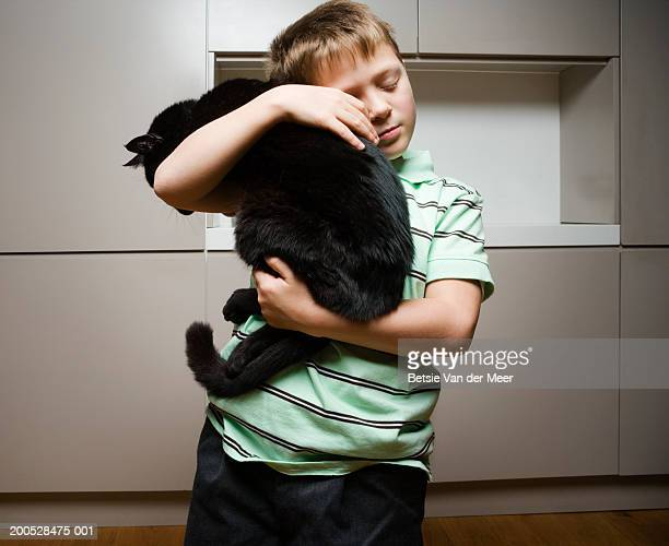 Boy (8-10) holding and cuddling black cat, eyes closed
