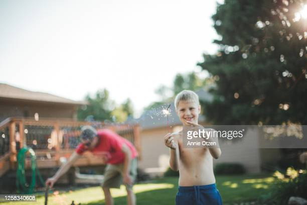 boy holding and pointing to a sparkler - sioux falls stock pictures, royalty-free photos & images