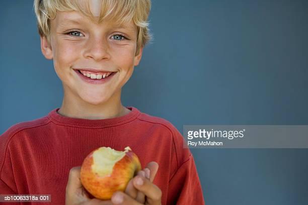 Boy (10-11 years) holding apple, portrait, studio shot