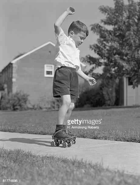 Boy holding arms out for balance, wearing metal roller-skates on sidewalk.