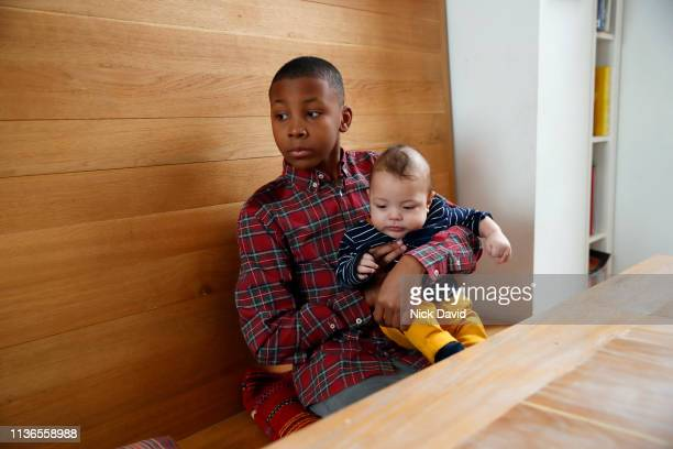Boy holding baby brother at kitchen table