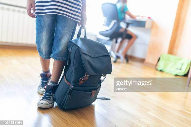 boy holding backpack moving away, low section - rucksack stock pictures, royalty-free photos & images