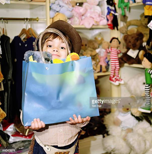 Boy (4-6) holding bag in toy store, portrait