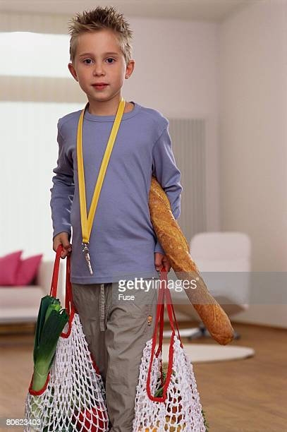 boy holding baguette and shopping bags - 網状 ストックフォトと画像