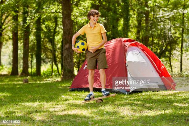 Boy holding ball playing by tent in forest