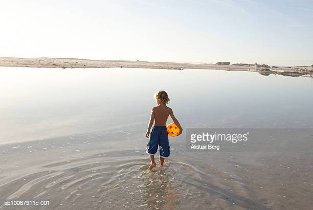 Boy (6-7 years) holding ball walking in shallow water, rear view