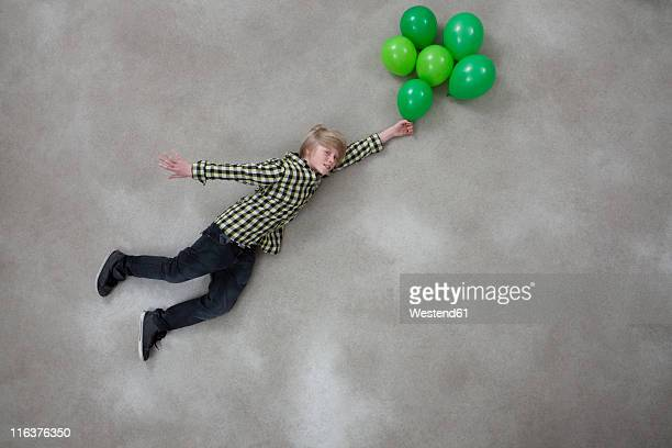 Boy holding balloons on gray background