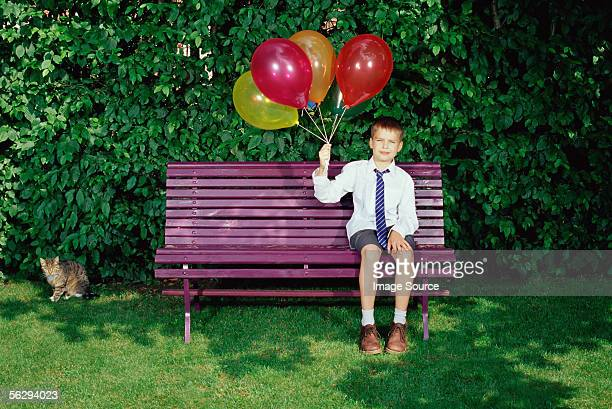 boy holding balloons - happy birthday cat stock photos and pictures