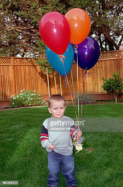 boy holding balloons - jessamyn harris stock pictures, royalty-free photos & images
