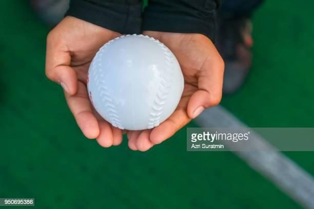 A boy holding baseball rubber ball