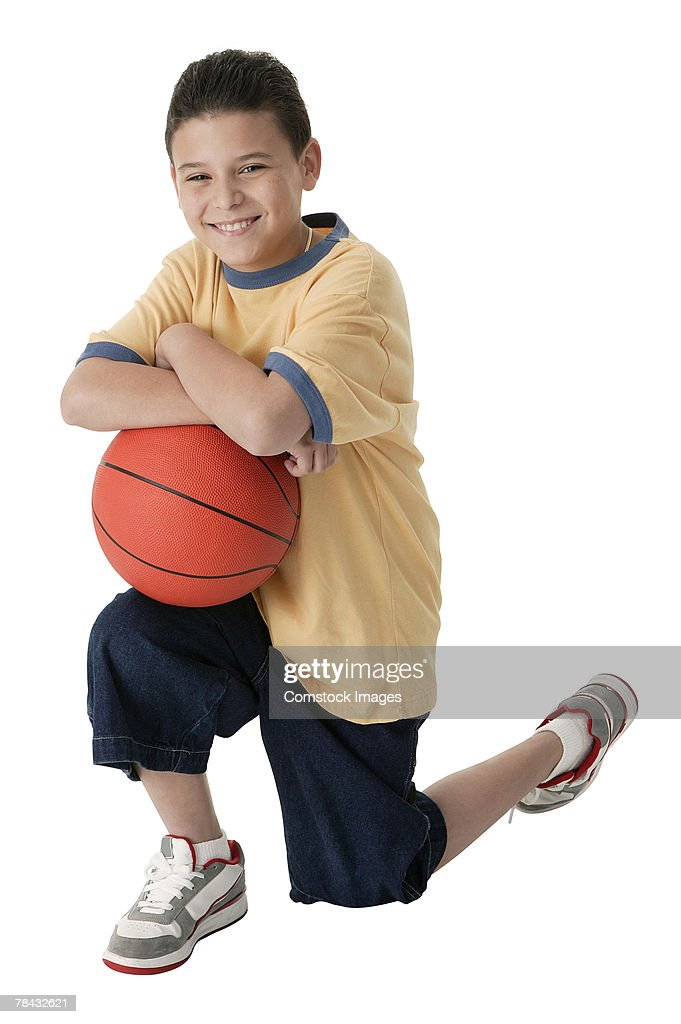 Boy holding basketball : Stockfoto