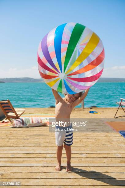 boy holding beach ball on houseboat sun deck, kraalbaai, south africa - children only stock photos and pictures