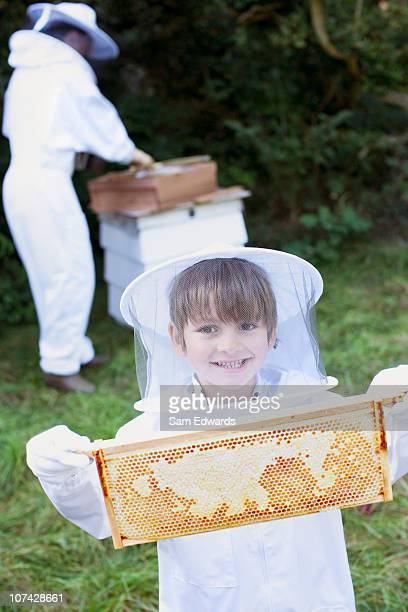 Boy holding bee hive honeycomb