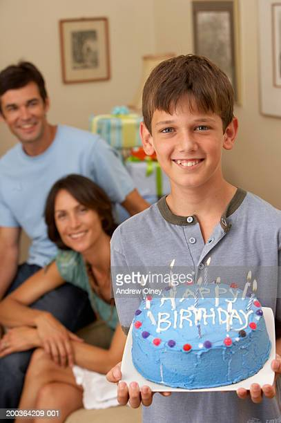 Boy (10-12) holding birthday cake, parents in background, smiling