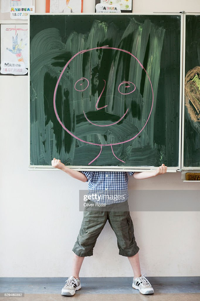 Boy holding blackboard with smiley face drawing : Stock Photo