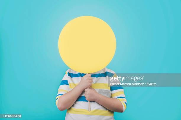 boy holding blank yellow placard against turquoise background - obscured face stock pictures, royalty-free photos & images