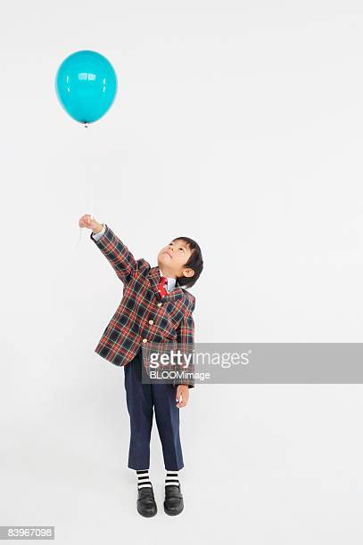 Boy holding blue balloon