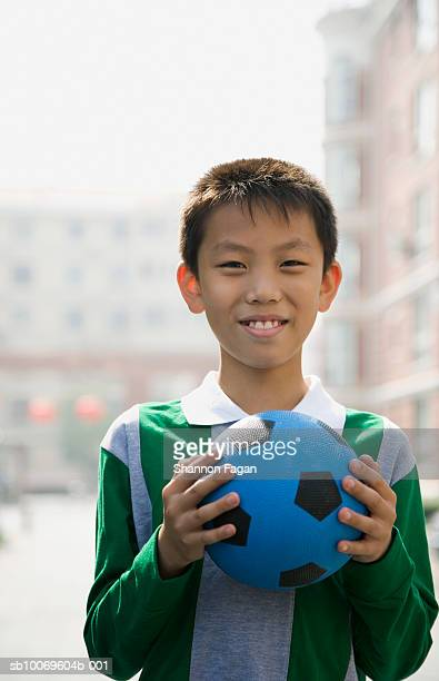 Boy (10-11) holding blue soccer ball in city, portrait