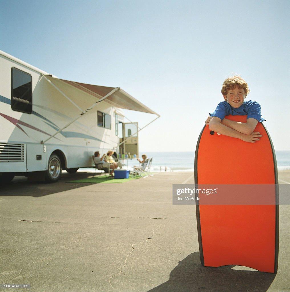 Boy Holding Boogie Board Family Rv Camping In Background
