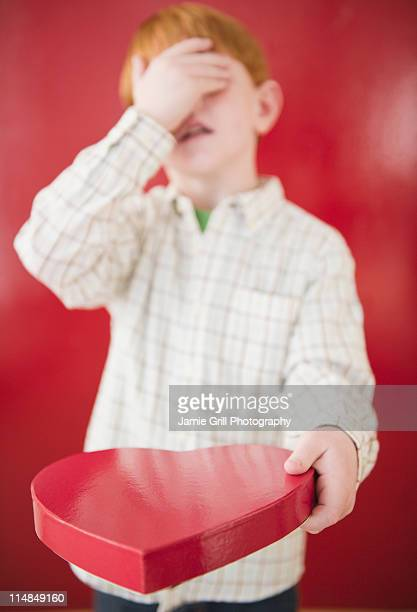 Boy (8-9) holding box of chocolates on Valentines Day