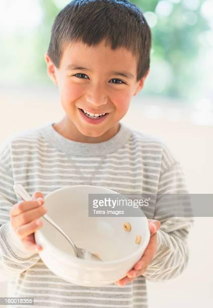 Boy (6-7) holding breakfast bowl